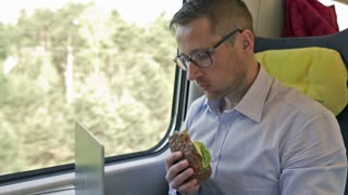 Businessman eating sandwich and working on laptop, steadycam shot