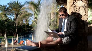 Businessman finish working with laptop computer by the waterfall on his vacation