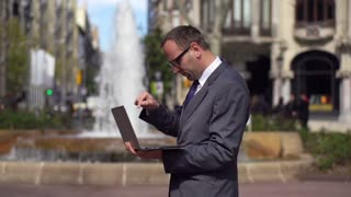 businessman finishing his work on laptop and walking away the fountain