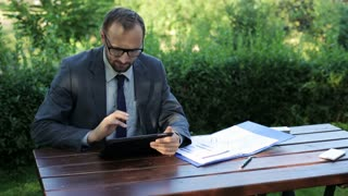 businessman finishing his work on tablet and smiling to the camera