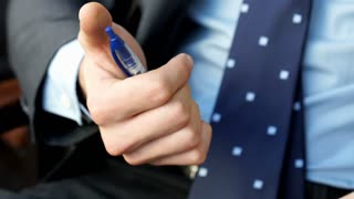 Businessman holding a pen and playing with it, steadycam shot
