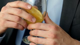Businessman holding glass with orange juice and drinking it, steadycam shot