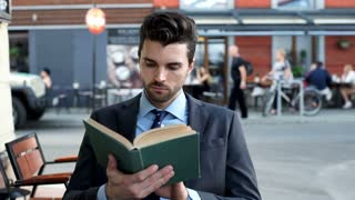 Businessman looking absorbed while reading book in the outdoor cafe, steadycam s