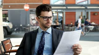 Businessman looking absorbed while reading papers, steadycam shot