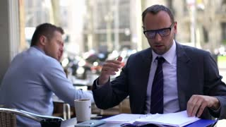 businessman looking at bad results in documents,sitting the cafe in a city