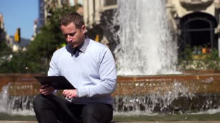 businessman looking at good results on tablet and sitting by the fountain