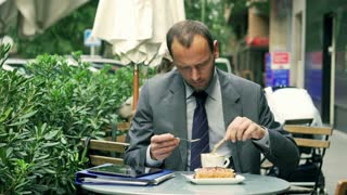 Businessman pouring sugar to the coffee in the street cafe