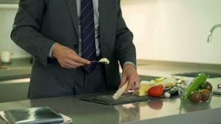 Businessman putting butter on the sandwich, steadycam shot