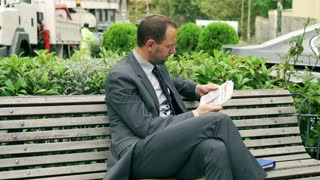 Businessman reading newspaper on the street bench