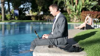 Businessman relaxing after work by the swimming-pool