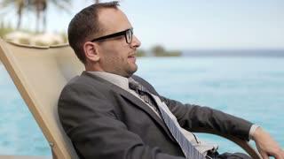 Businessman relaxing on sunbed in tourist resort, steadycam shot