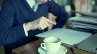 Businessman sitting at the table and reading documents, steadycam shot
