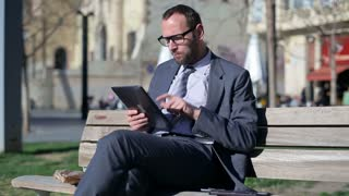 Businessman sitting on street bench using tablet and smiling to camera.