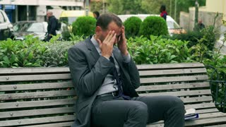 Businessman sitting on the bench and having headache