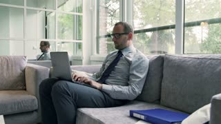 Businessman sitting on the sofa at home and working on laptop