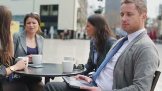 Businessman smiling to camera and sitting with colleagues in street cafe