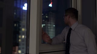 Businessman standing next to the window and looking at night