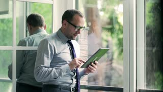 Businessman standing next to the window and using tablet