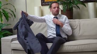 businessman taking clothes off after work and sitting on the sofa