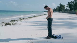 Businessman taking off his trousers on the beach, steadycam shot