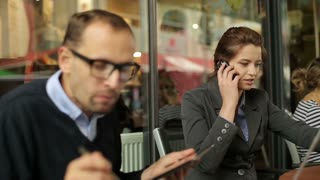 Businessman talking on cellphone and eating lunch in cafe, outdoor