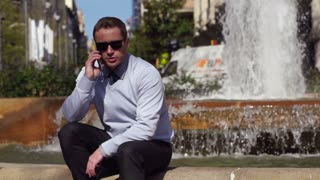 businessman talking on the phone and sitting by the fountain, slow motion 60fps