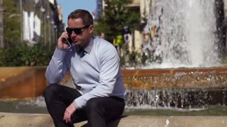 businessman talking on the phone  sitting by the fountain, slow motion  240fps