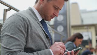 Businessman touching screen on cellphone by stylus, steadycam shot