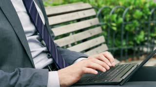 Businessman typing on keyboard on the bench, closeup, steadycam shot