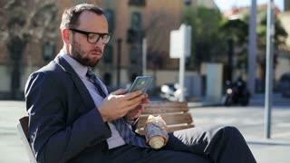 Businessman using cellphone eating baguette on street bench, steadycam shot.