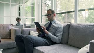 Businessman using tablet and smiling to the camera on the couch