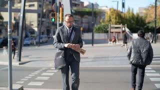 Businessman walk as pedestrian cross street stop eating baguette and go.
