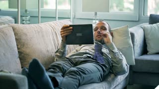 Businessman watching funny movie on tablet and lying on the sofa