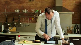 businessman with a tablet eating a sandwich in the kitchen