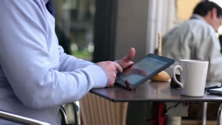 businessman with a tablet sitting outside the cafe and smiling to the camera