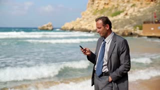 Businessman with cellphone walking on the beach