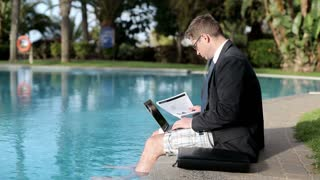 Businessman with laptop and documents on his vacation by the swimming pool