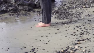 Businessman without shoes standing on stony beach, slow motion shot at 240fps