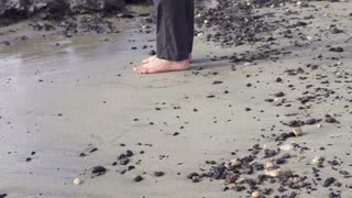 Businessman without shoes standing on stony beach, slow motion shot at 60fps