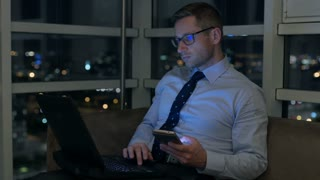 Businessman working late on modern technology in the apartment