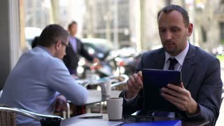 businessman working on a tablet and sitting outside the cafe
