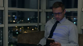 Businessman working on modern technology at night