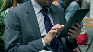 Businessman working on tablet and drinking coffee, steadycam shot