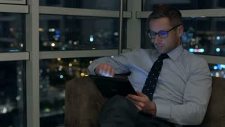 Businessman working on tablet in the apartment at night