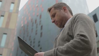 Businessman working on tablet in the city