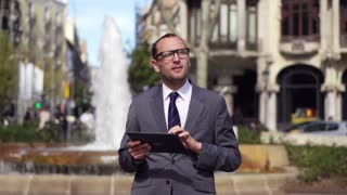 businessman working on tablet, standing back to the fountain, slow motion 240fps