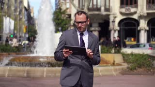businessman working on tablet standing back to the fountain, slow motion 60fps