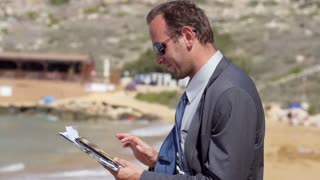 Businessman working on the beach with tablet slow motion shot at 240fps