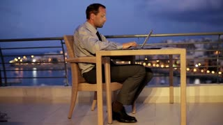 Businessman working with laptop on the terrace in the evening, crane shot