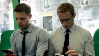 Businessmen traveling by bus and using smartphones, steadycam shot